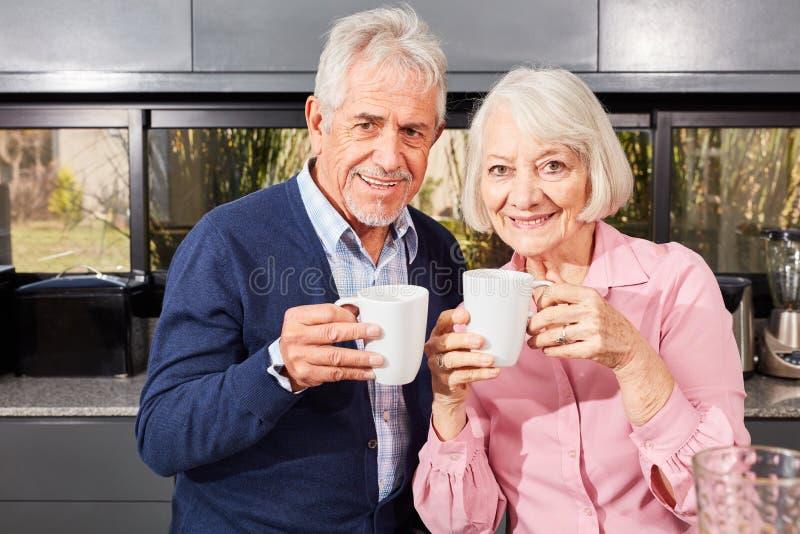 Hoger paar met mok koffie in de keuken stock foto's