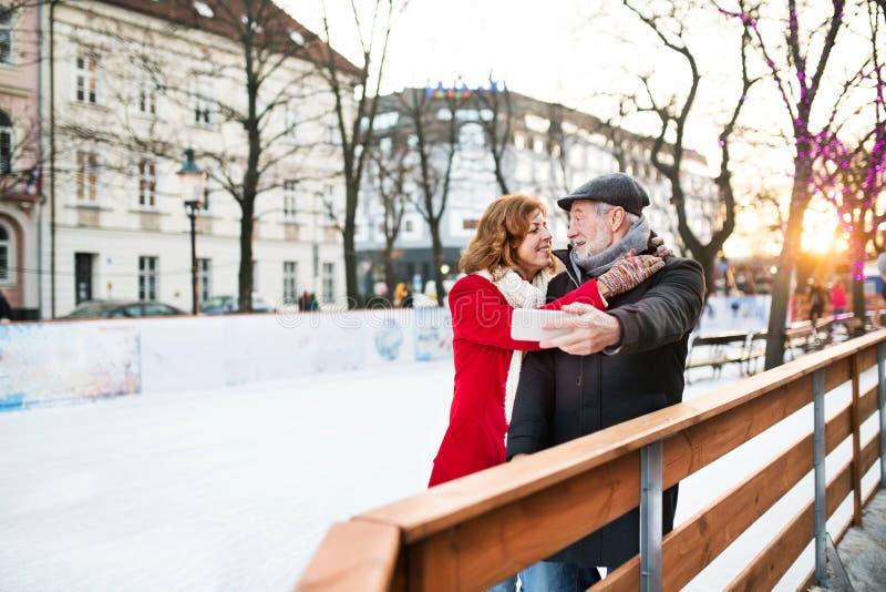 Hoger paar met smartphone op een gang in een stad in de winter royalty-vrije stock afbeelding