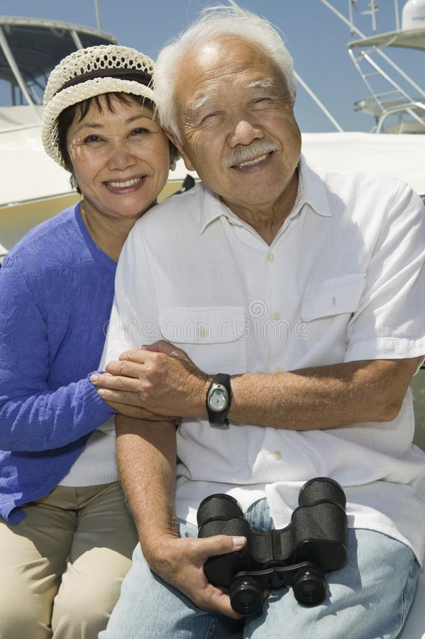 Hoger paar met verrekijkers op boot stock fotografie
