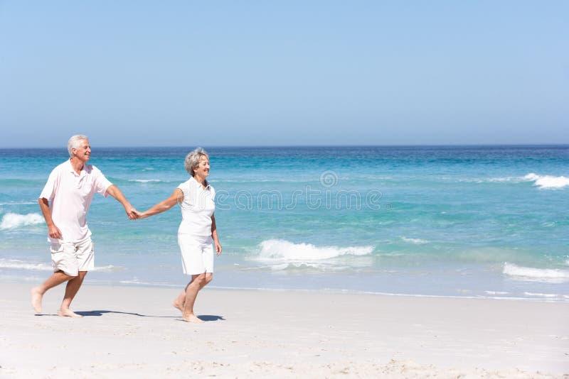 Hoger Paar op Vakantie die langs Zandig Strand loopt stock afbeelding