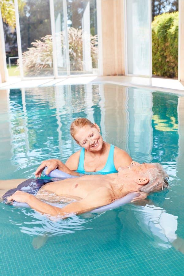 Hoger paar in pool die samen watergeneeskunde maken royalty-vrije stock foto's