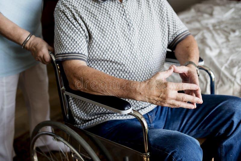 Hoger paar, vrouw die een rolstoel van haar echtgenoot duwen stock fotografie