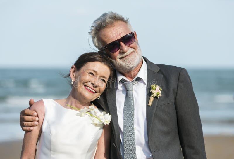 Hoger paar worden die die bij het strand wordt gehuwd stock fotografie