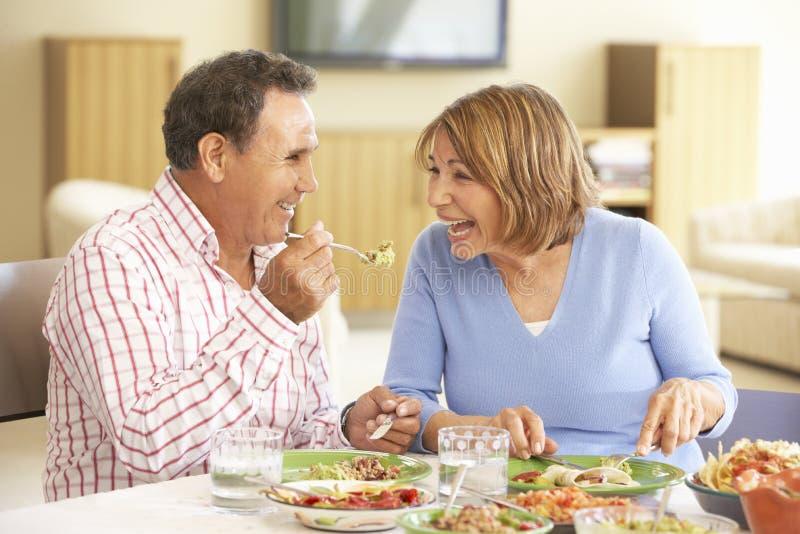 Hoger Spaans Paar die van Maaltijd thuis genieten stock foto's