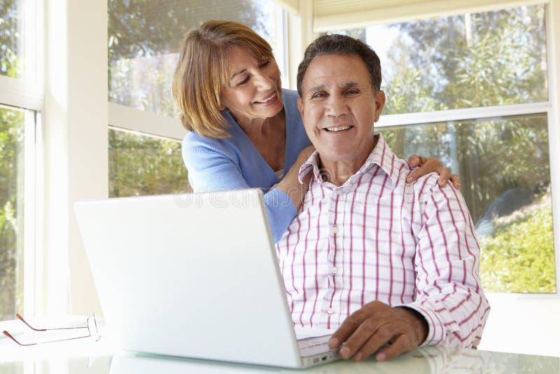 Hoger Spaans Paar in Huisbureau met Laptop stock afbeelding
