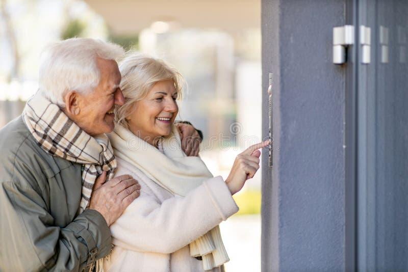 Hoger stel dat de deurbel naar hun gasthuis belt stock fotografie