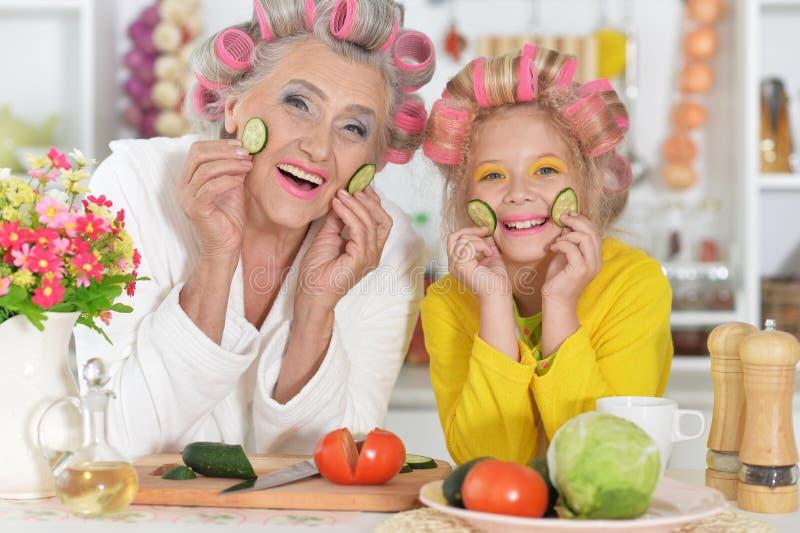 Hoger vrouw en meisje met roze haarkrulspelden op hoofd stock foto