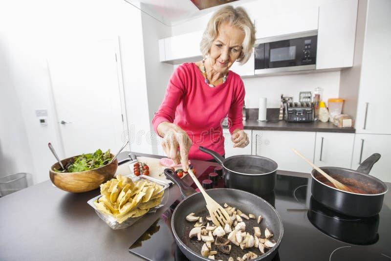 Hoger vrouwen kokend voedsel in keuken stock foto