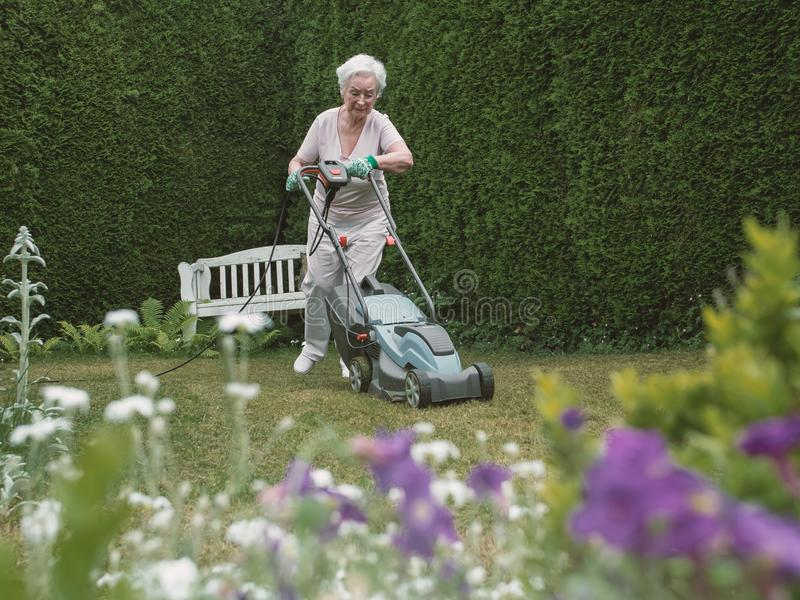 Hoger vrouwen maaiend gras stock foto's