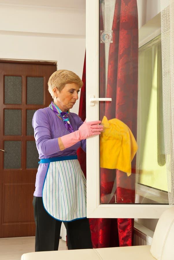 Hoger vrouwen schoonmakend venster royalty-vrije stock afbeelding