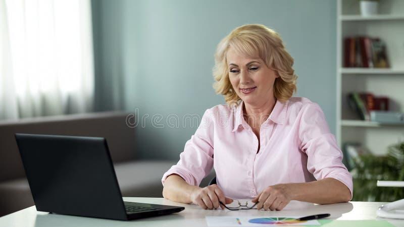 Hoger wijfje die freelancer aan laptop thuis werken, succesvolle bedrijfsdame stock fotografie