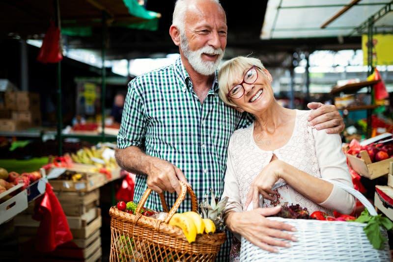 Hoger winkelend paar met mand op de markt Gezond dieet royalty-vrije stock afbeeldingen