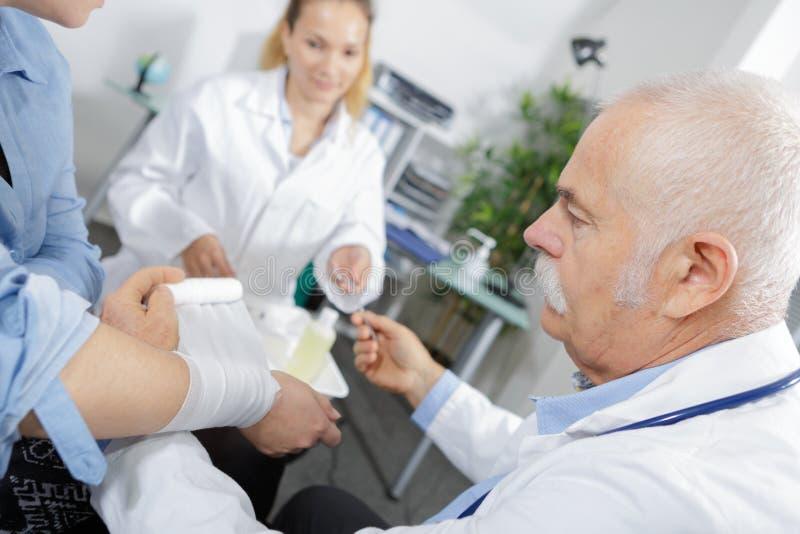 Hogere arts die hand met polskneuzing verbinden stock afbeelding
