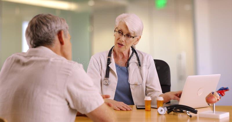Hogere arts die met bejaarde in het bureau spreken royalty-vrije stock foto's