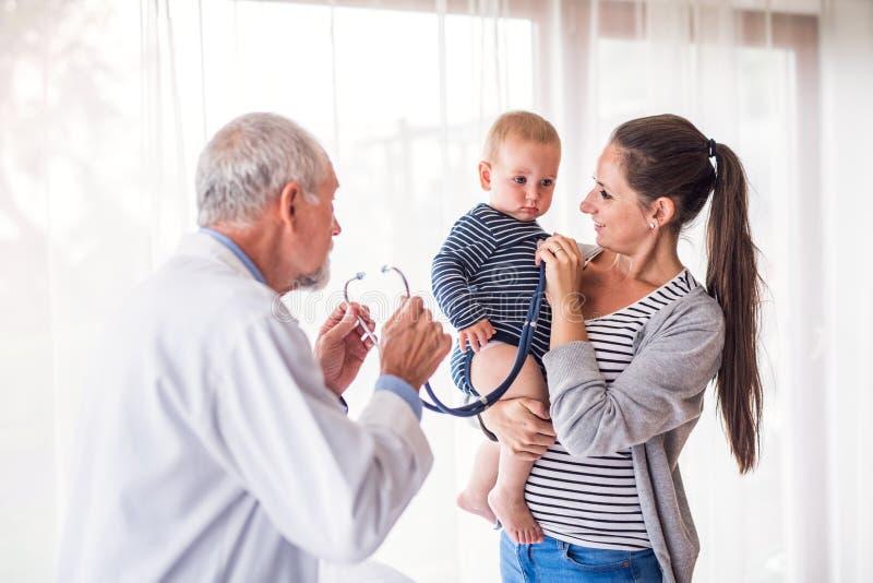 Hogere arts, moeder en een babyjongen in een bureau stock fotografie