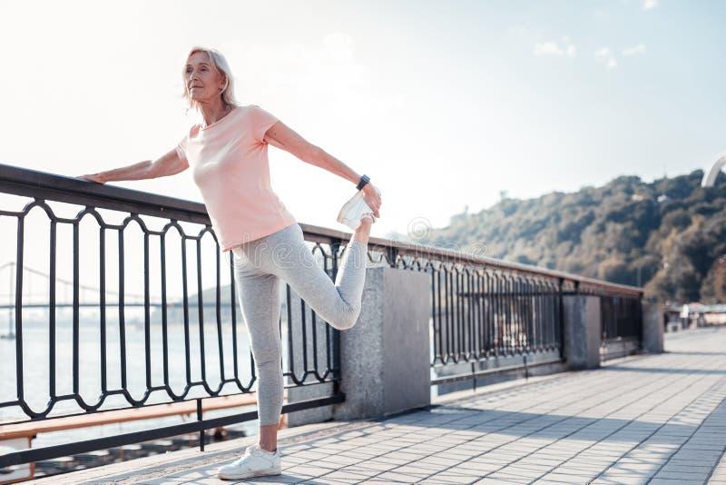 Hogere atletische vrouwenholding door de het omheinen en het doen oefeningen stock foto's