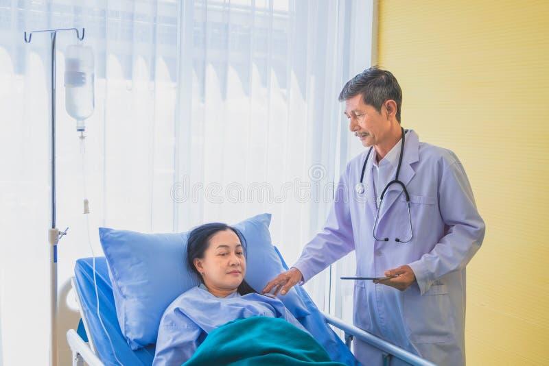 Hogere Aziatische mannelijke arts die en met vrouwelijke patiënt op middelbare leeftijd op Afdeling bezoeken spreken royalty-vrije stock afbeelding