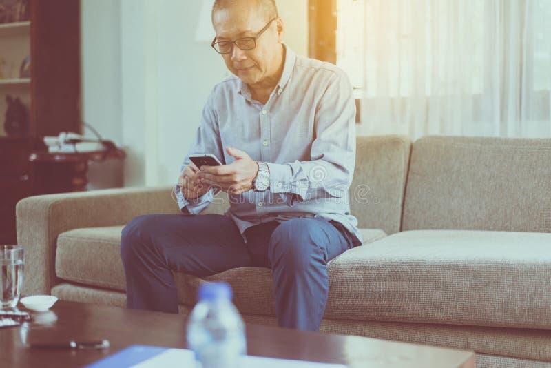 Hogere Aziatische mens die rust hebben en tijd ontspannen, Gelukkig en smartphone verbindend Internet gebruiken die thuis, glimla stock afbeelding