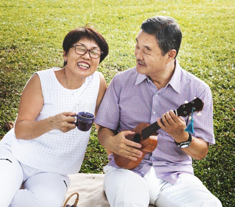 Hogere Aziatische paar speelmuziek in een park stock afbeelding