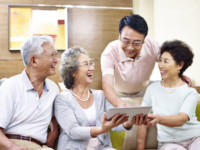 Hogere Aziatische paren die tabletcomputer met behulp van stock foto's