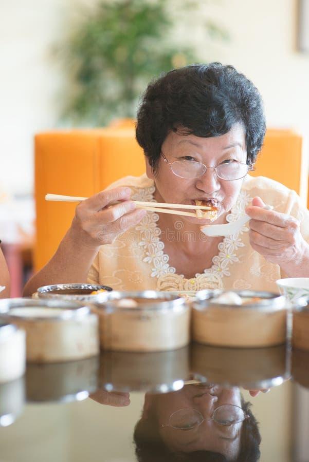 Hogere Aziatische Vrouw die bij restaurant dineren royalty-vrije stock afbeelding