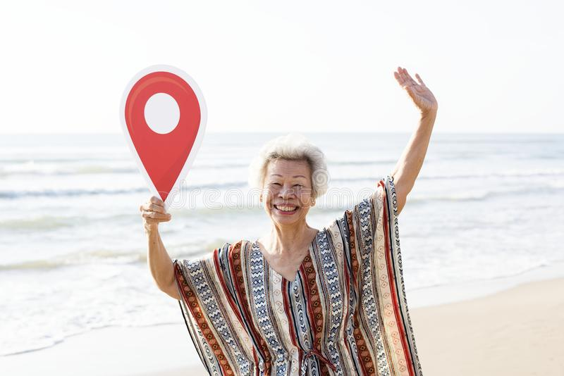 Hogere Aziatische vrouw die binnen bij het strand controleren stock afbeeldingen