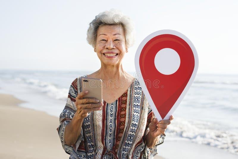 Hogere Aziatische vrouw die binnen bij het strand controleren royalty-vrije stock foto's