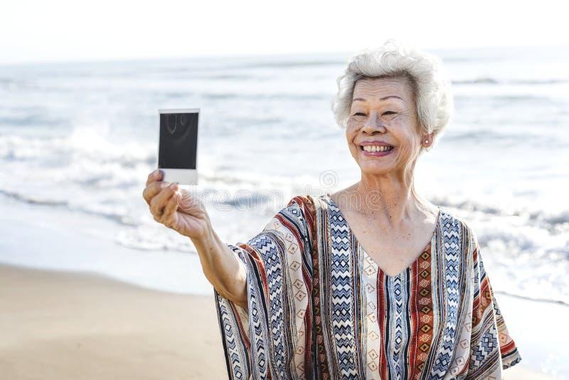 Hogere Aziatische vrouw die een foto houden stock foto