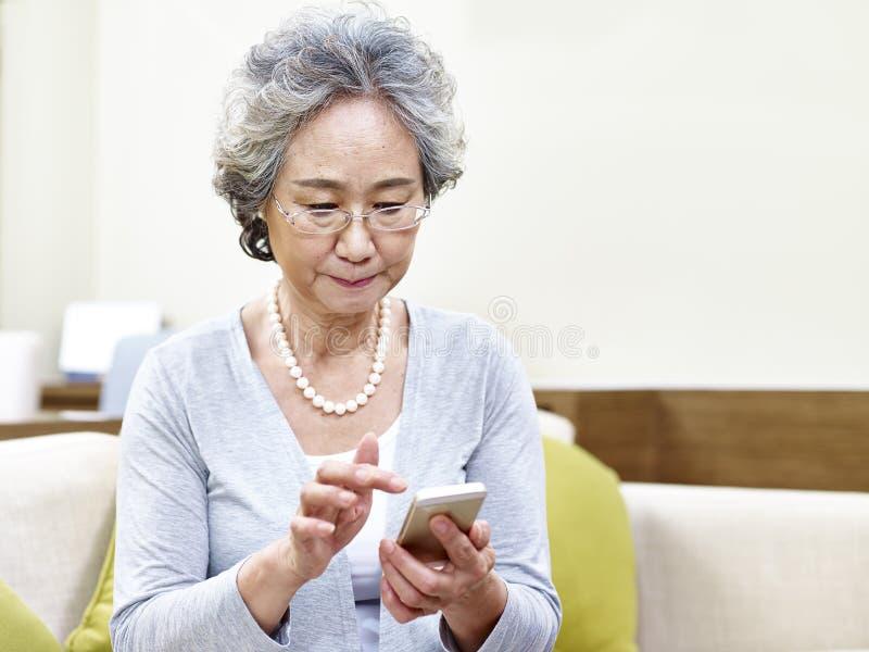 Hogere Aziatische vrouw die mobiele telefoon met behulp van royalty-vrije stock fotografie