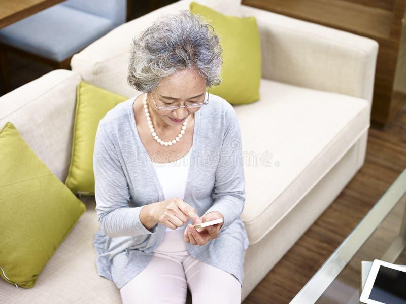 Hogere Aziatische vrouw die mobiele telefoon met behulp van royalty-vrije stock foto's