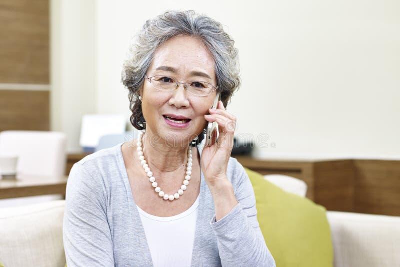 Hogere Aziatische vrouw die op cellphone spreken stock afbeeldingen