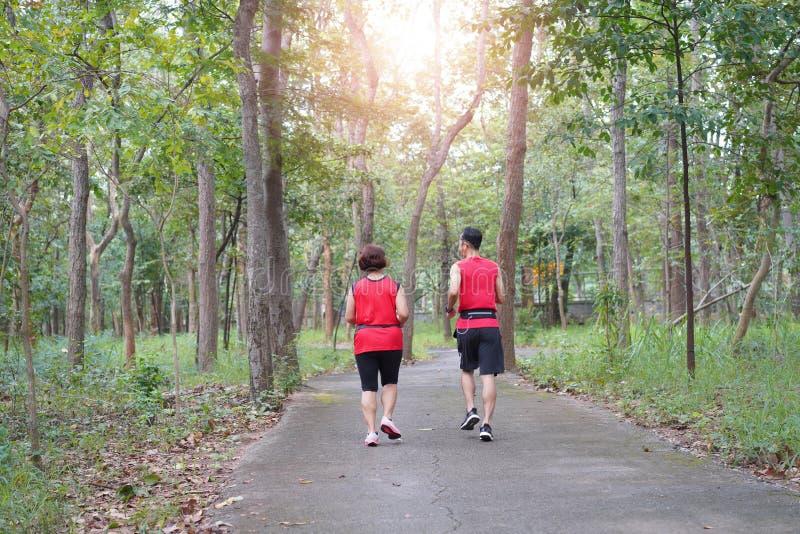 Hogere Aziatische vrouw met mens of persoonlijke trainerjogging die in het park de lopen stock fotografie