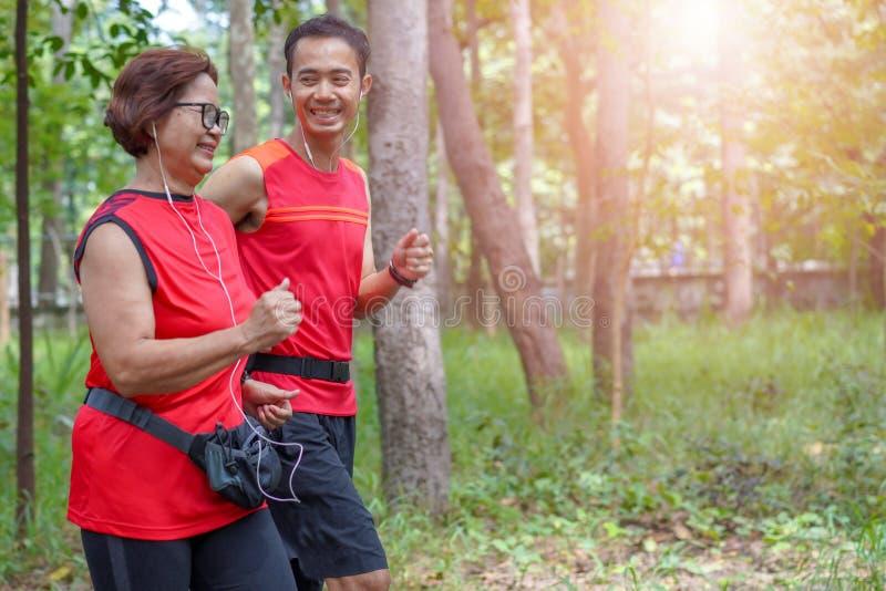 Hogere Aziatische vrouw met mens of persoonlijke trainerjogging die in het park de lopen stock afbeelding