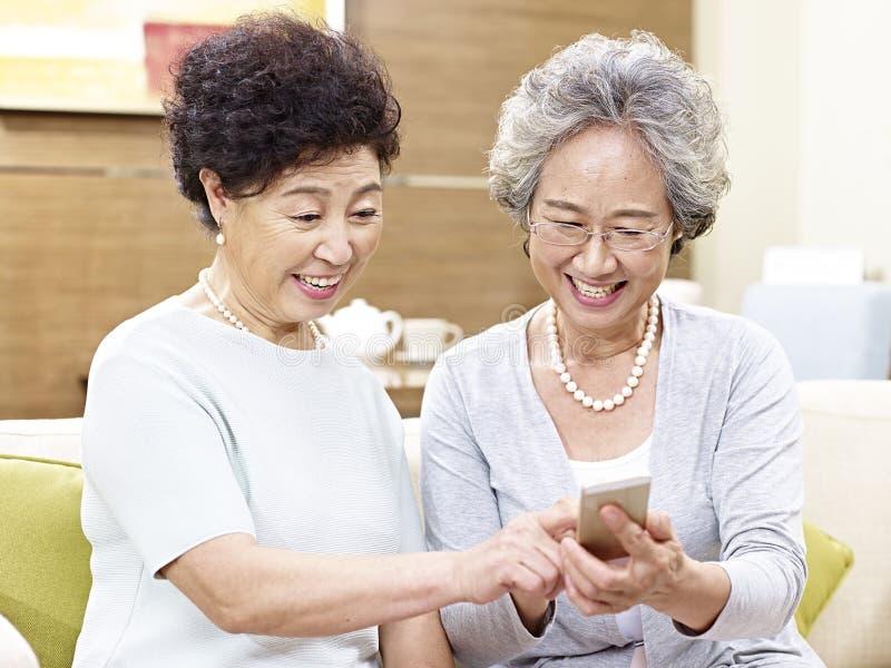 Hogere Aziatische vrouwen die mobiele telefoon met behulp van royalty-vrije stock foto's