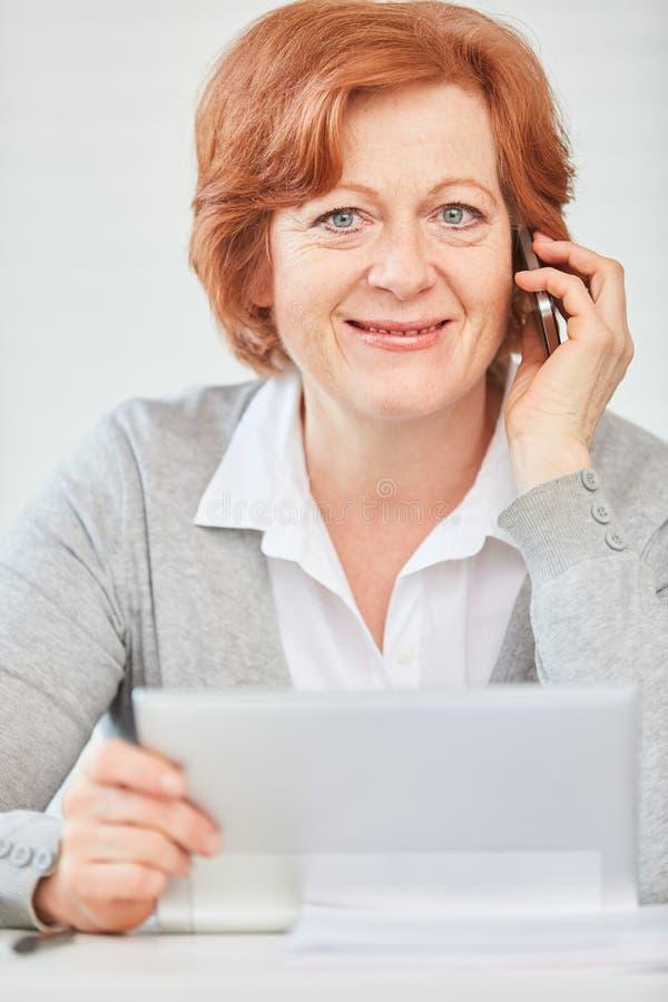 Hogere bedrijfsvrouw die met smartphone roepen royalty-vrije stock afbeelding
