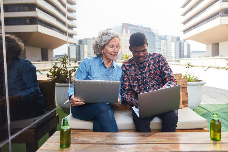 Hogere bedrijfsvrouw en intern op laptop royalty-vrije stock foto