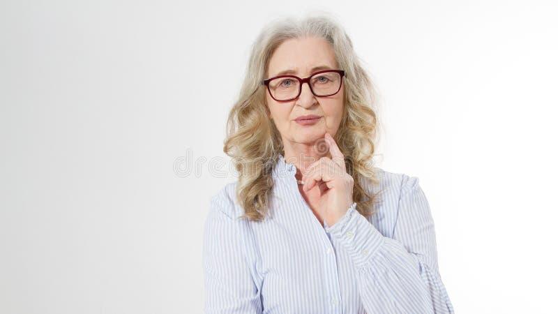 Hogere bedrijfsvrouw met modieuze glazen en rimpelgezicht op witte achtergrond Rijpe gezonde dame De ruimte van het exemplaar oud stock foto's