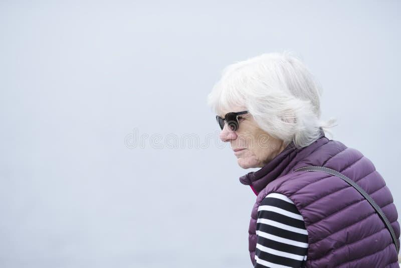 Hogere bejaarde dame die droevig en eenzaam tegen lege duidelijke hemel als achtergrond denken stock afbeeldingen