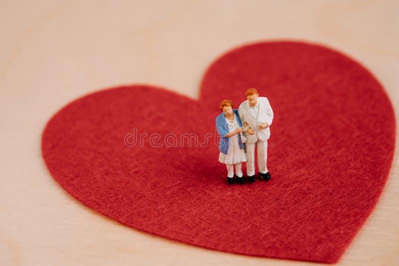 Hogere bejaarde gezondheidszorg, verzorger of gelukkig pensioneringsconcept, de miniatuurmens van het mensen gelukkig paar en dam stock afbeeldingen