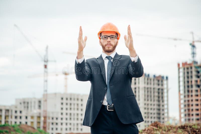 Hogere bouwer die in bouwvakkers in openlucht richten royalty-vrije stock afbeeldingen