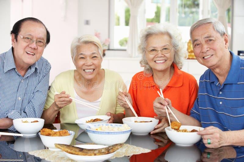 Hogere Chinese Vrienden die Maaltijd thuis eten stock afbeeldingen