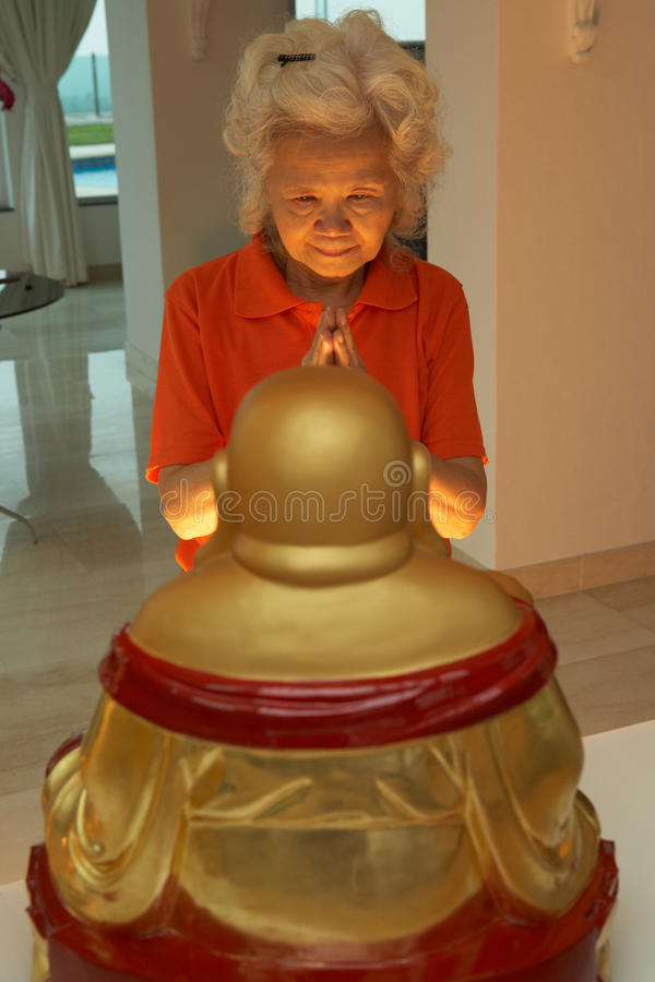 Hogere Chinese Vrouw die aan Standbeeld van Boedha bidt stock foto's