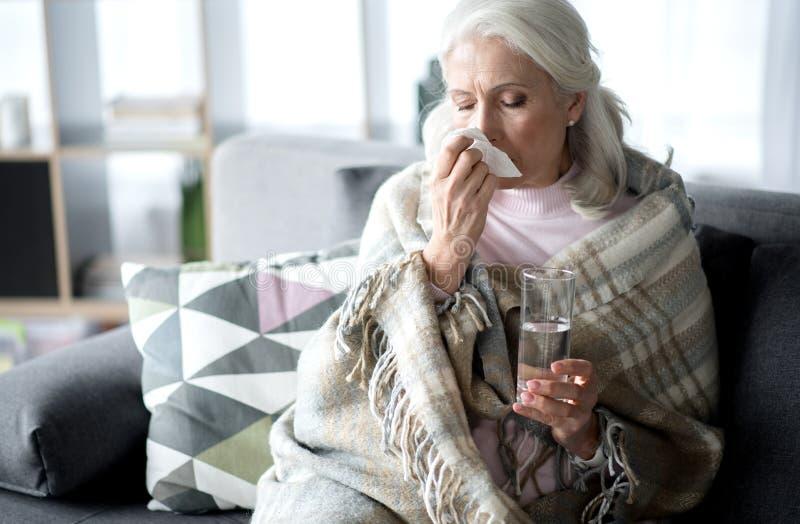 Hogere dame die aan verwarmingspijp thuis lijden stock foto
