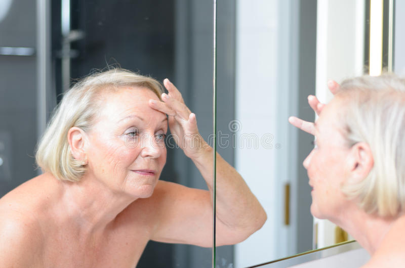 Hogere dame die haar huid in de spiegel controleren royalty-vrije stock foto's