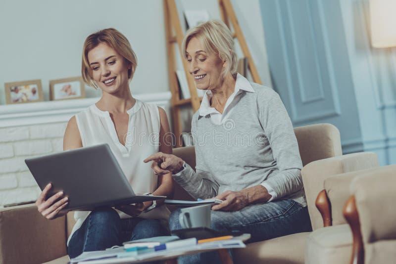 Hogere dame die op het laptop scherm van jonge vrouw richten stock foto