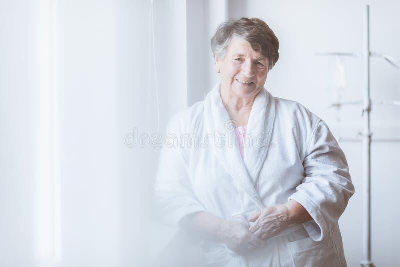 Hogere dame die witte badjas dragen die zich door het venster bij verpleeghuis bevinden royalty-vrije stock foto