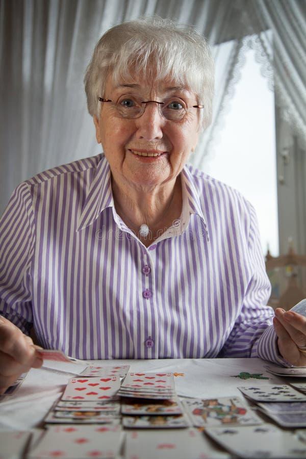 Hogere dame het spelen patiencekaarten thuis royalty-vrije stock afbeeldingen