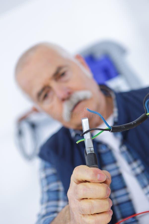 Hogere de buigtang van de elektricienholding in hand het snijden elektrische draden royalty-vrije stock foto