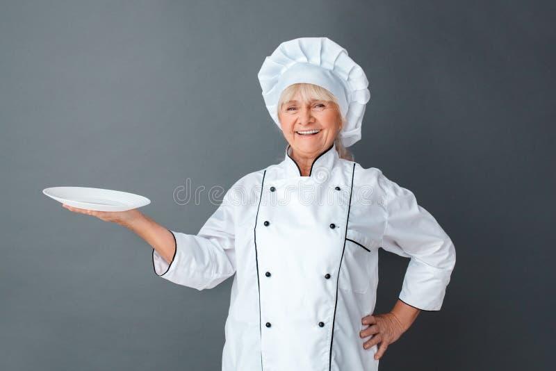 Hogere de studio van de vrouwenchef-kok status geïsoleerd op grijze holdingsplaat die camera vrolijk lachen kijken stock fotografie