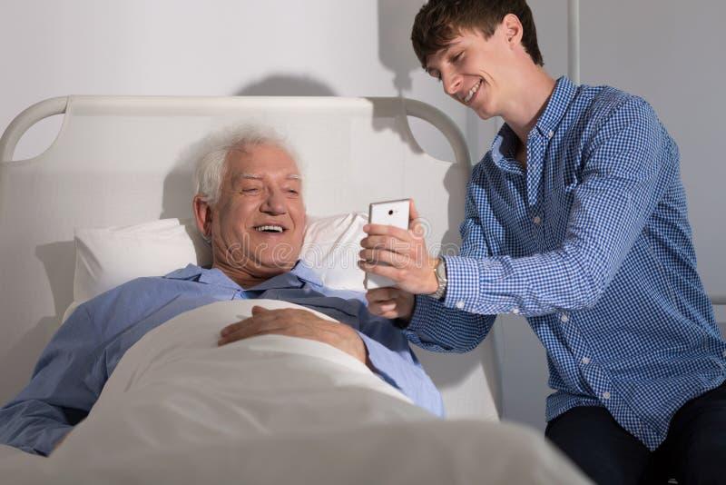Hogere die patiënt door familie wordt bezocht stock foto